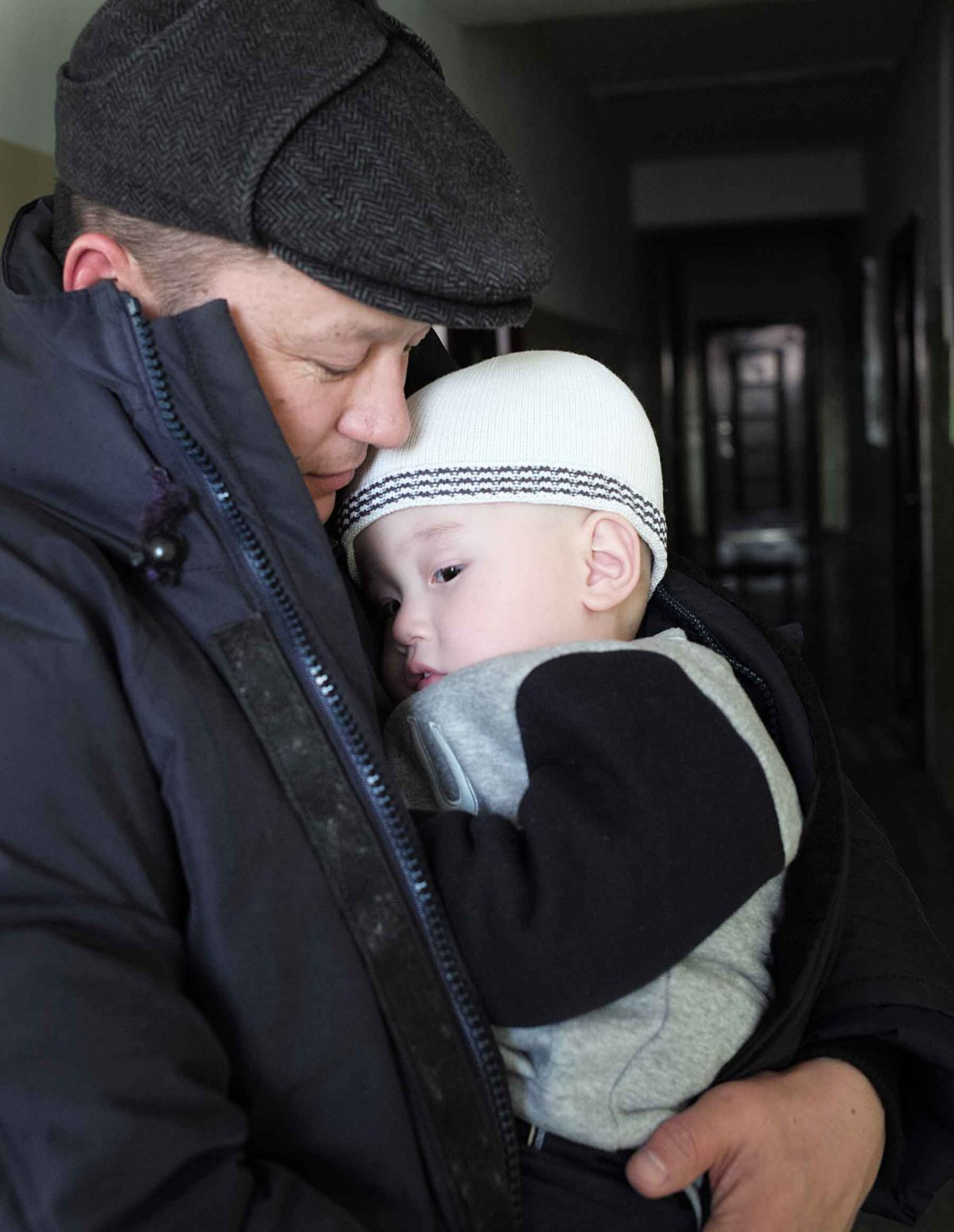 The family moved from their summer home and rented a small two-roomed flat which they were able to heat more easily and keep him warm. Here Dad is taking him in his arms to keep him warm during a short walk in the winter.